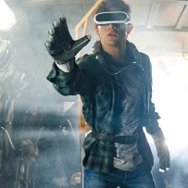 Man with big screen-like goggles like virtual reality headgear with a big glove stretched out on his hand