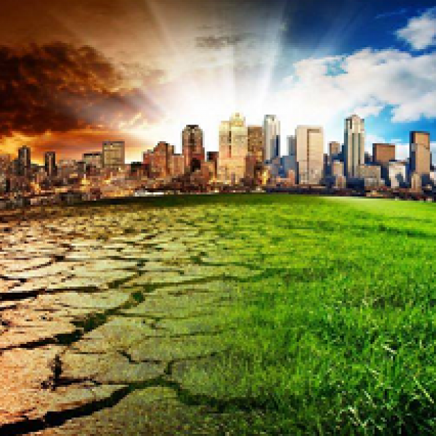 A cityscape against a horizon with sunrays shooting from the ground to a blue sky on right and fiery sky on left with the fore ground at right green grass and at left cracked and dry