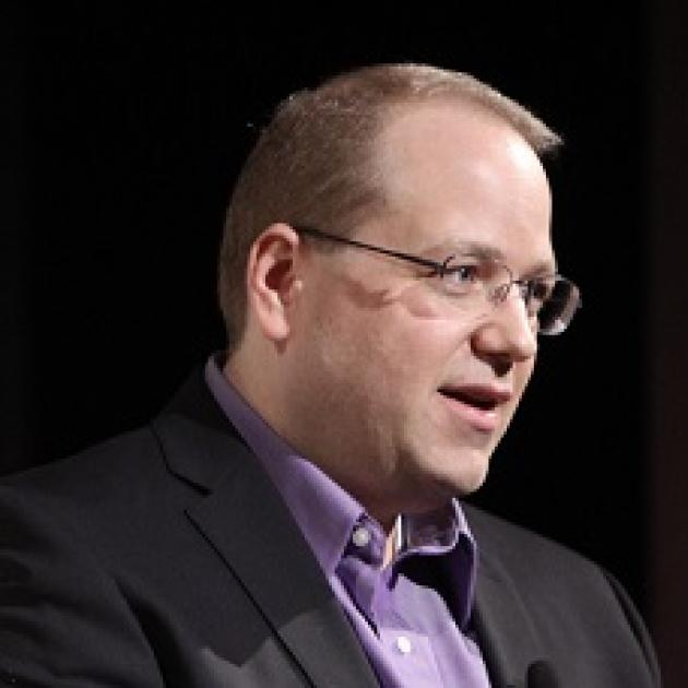 Middle aged white man with brown receding hair with wire rimmed glasses looking to the right with  a gray suitcoat and purple shirt his mouth open as if talking