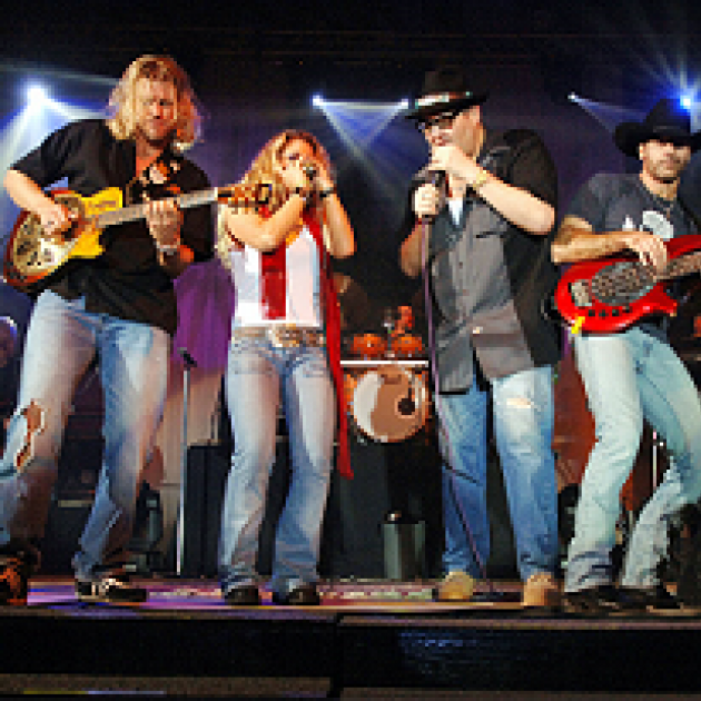 Four guy onstage playing guitars, harmonica and singing wearing cowboy type of clothes