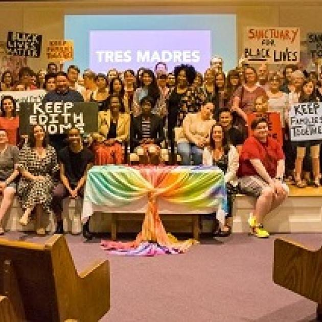 Many people posing inside a church with colorful banners and sign  about Keep Edith Home