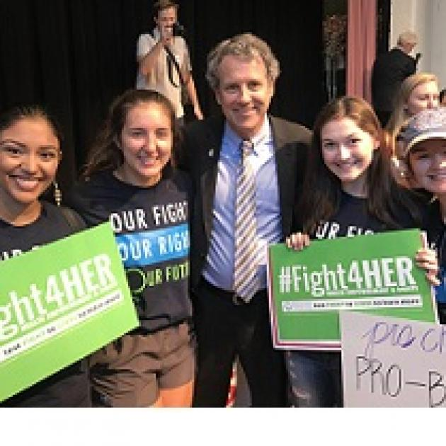 Three young women with #Fight4HER signs and one older white man in a suit
