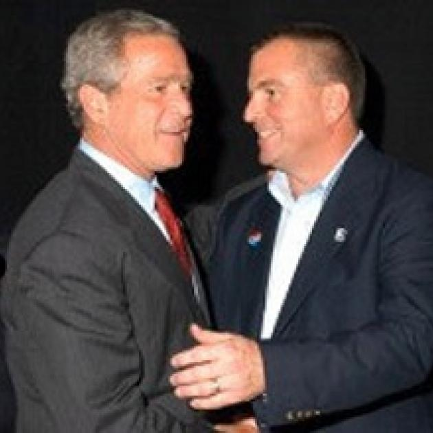 Two middle aged white men shaking hands very close together