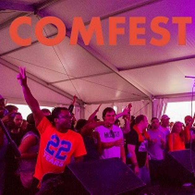 Purplish and reddish hues in a photo of several young people, black and white, holding their fingers as peace signs in the air, cheering and clapping under a tent with the words COMFEST in orange at top