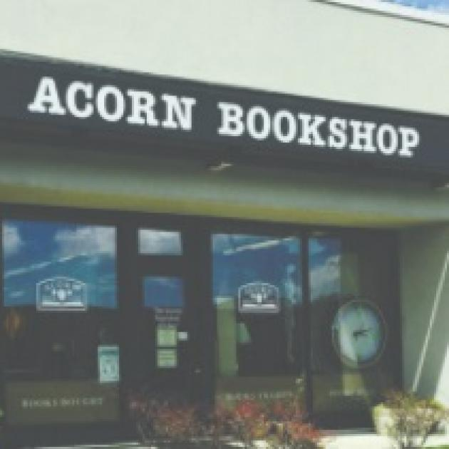 Front of a building with ACORN BOOKSHOP on the sign, windows and a front door of glass, flowers out front.