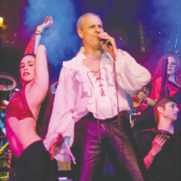 Middle aged white man with balding head wearing a blousy tie-front white shirt with tight shiny dark pants with a woman dancing sideways wearing a red bikini top and low-rider black pants and others dancing behind
