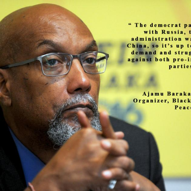 Bald black man with hands folded in front of chin, wearing glasses and with a gray goatee against yellow background and some words