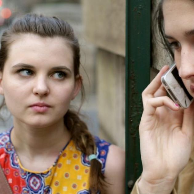 A woman on the phone and another woman looking at her in an alarmed way
