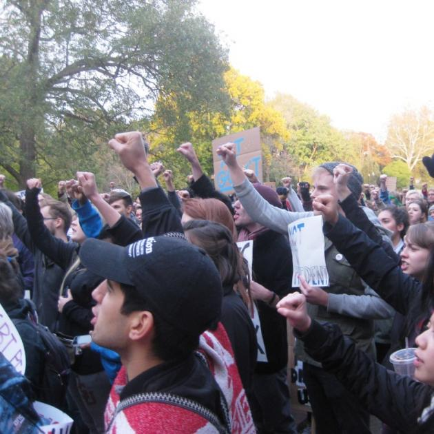 People with their fists in the air at an anti-Trump rally