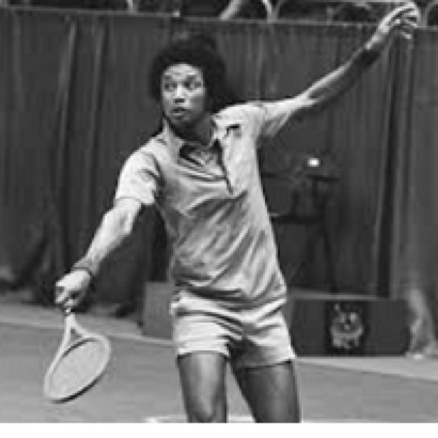 Black and white photo of young black man with afro playing tennis