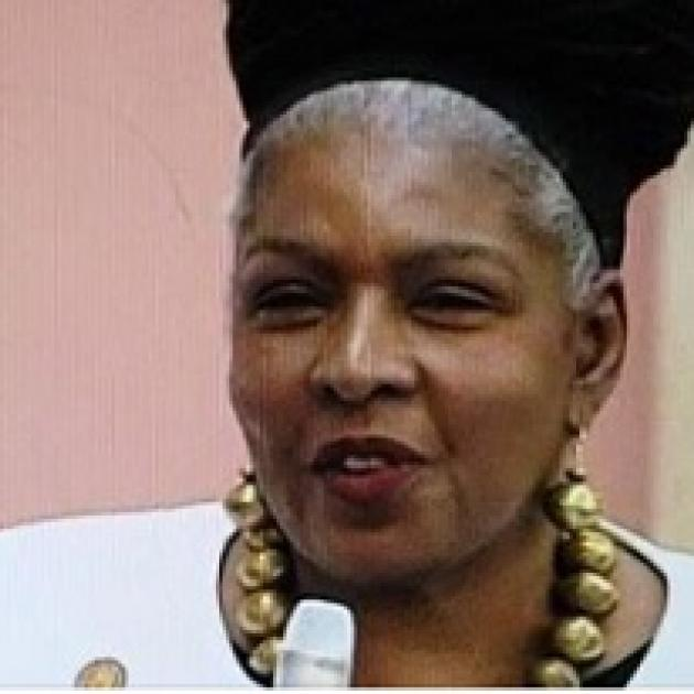 Black woman with A large gold necklace talking into a mic