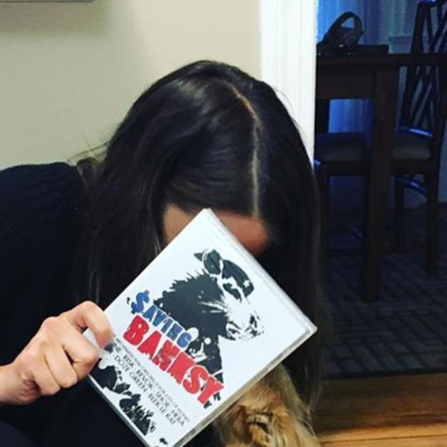 Women with dark hair leaning over hiding her face with a book, Saving Banksy