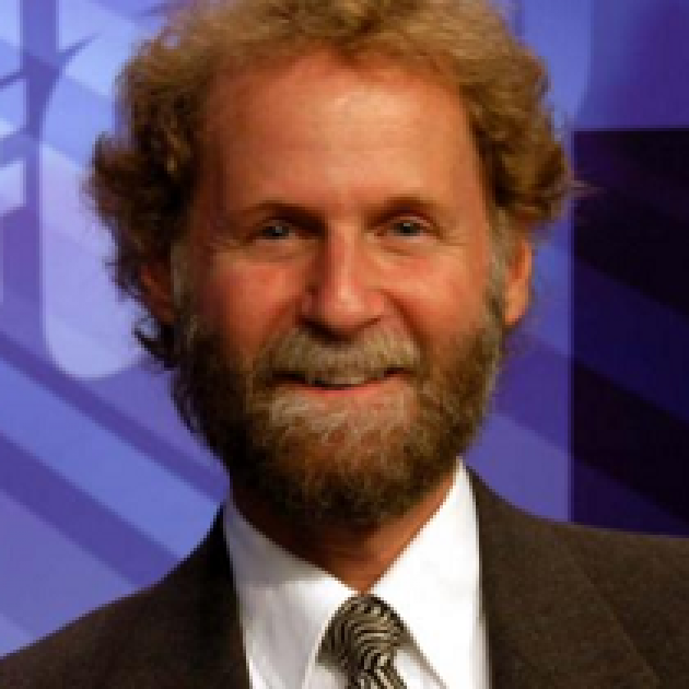 Photo of man with light brown curly hair and moustache and beard smiling in a suit