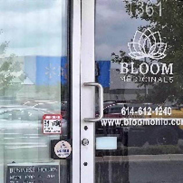 Glass front door of business with words Bloom Medicinals