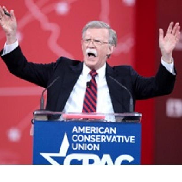 Older man with gray hair and long white mustache standing at a podium with his mouth  open waving both hands in the air and the words American Conservative Union on the podium