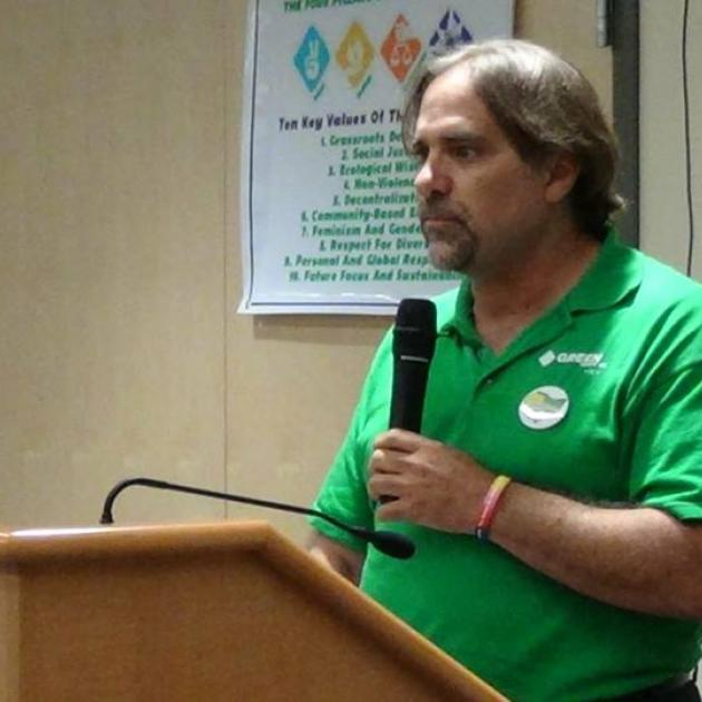 White man with goatee and dark hair in green shirt holding a mic at the podium