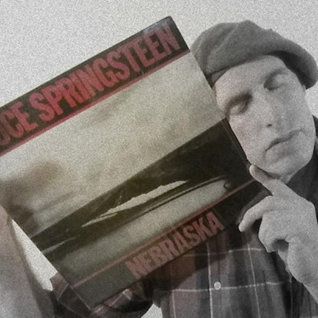 Guy wearing a beret with his eyes closed holding an album cover of Springsteen's Nebraska up to his face