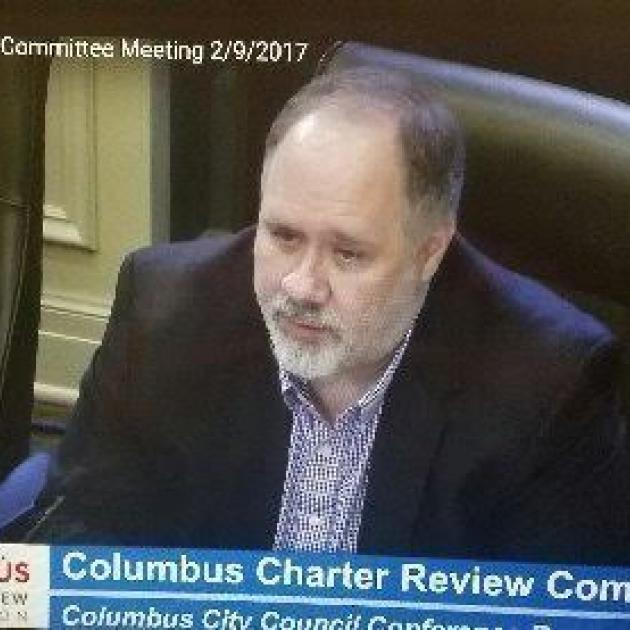 Bald man with gray goatee at a official city meeting