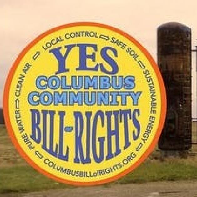 Round yellow logo with words Yes Columbus Community Bill of Rights and a fracking well in background
