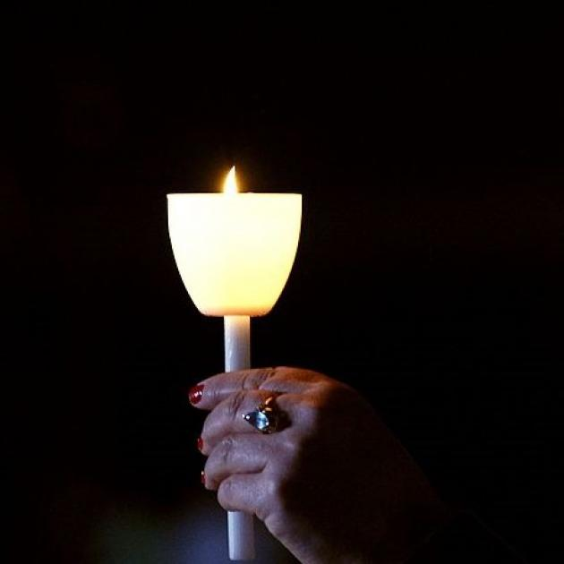 A hand holding up a candle in the dark