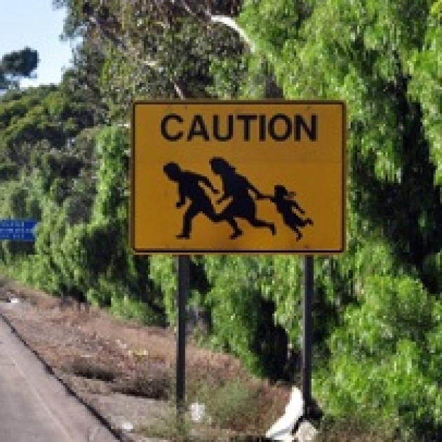 Yellow sign by the road and a hill with silhouettes of a family holding hands and running and the words CAUTION