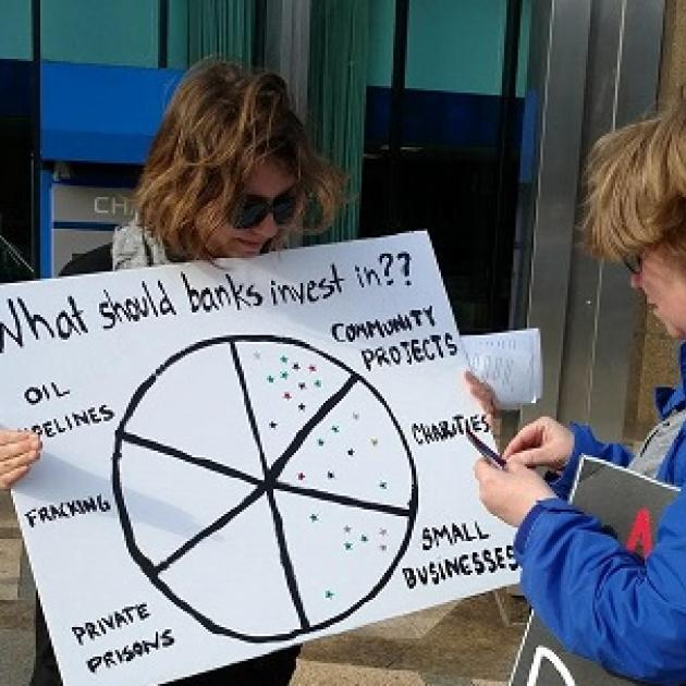 Girl holding sign about how Chase bank makes investments