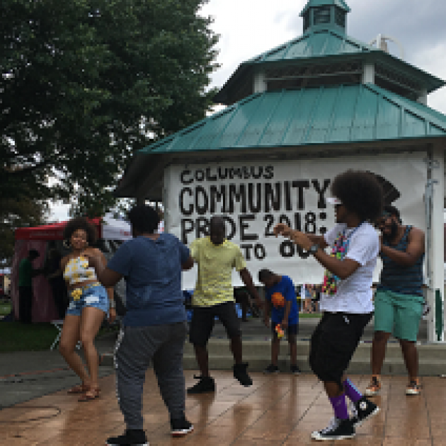 Young black people dancing outside in front of a gazebo with a Columbus Community Pride banner