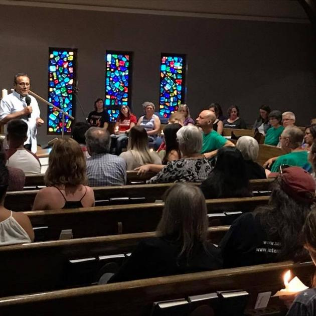 Man in white shirt talking into a mic at the far left side and a congregation of people sitting in pews and three stained glass windows in the back