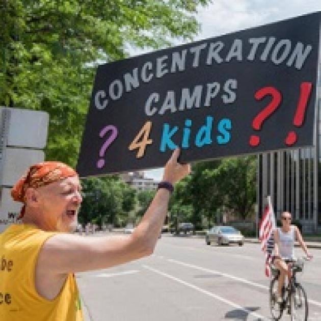 White man in a bandanna and yellow shirt yelling and holding a sign that reads Concentration Camps 4 Kids with lots of question marks