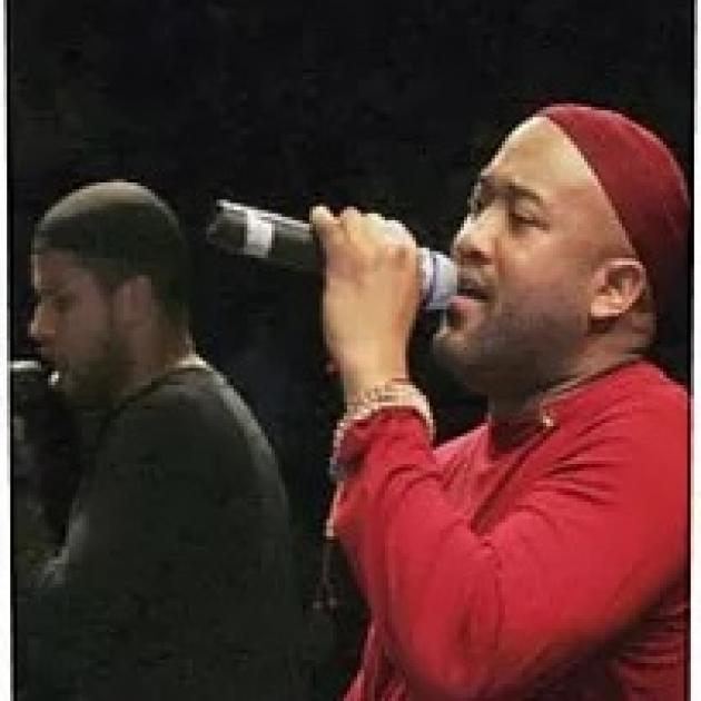 Black men in concert, one in red singing into mic