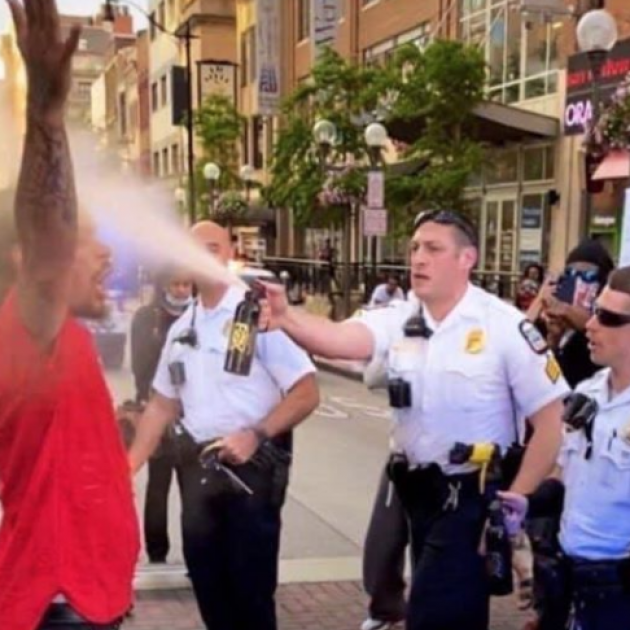 Cop spraying black man with hands in air