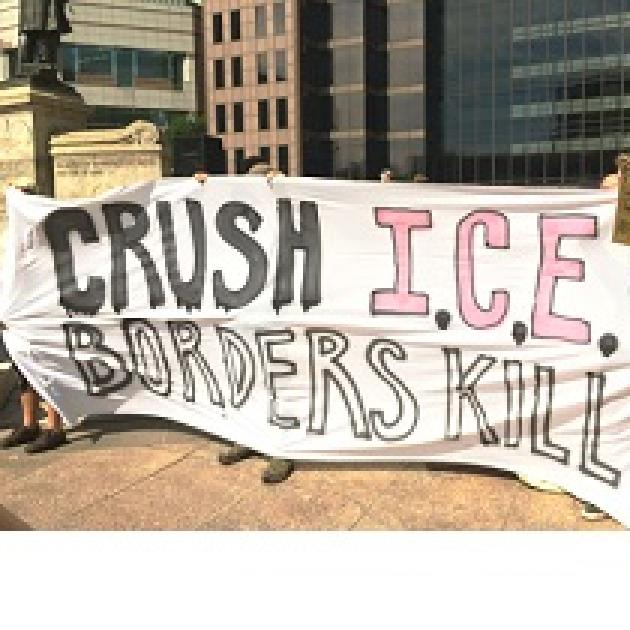 People at rally holding banner reading Crush ICE borders kill