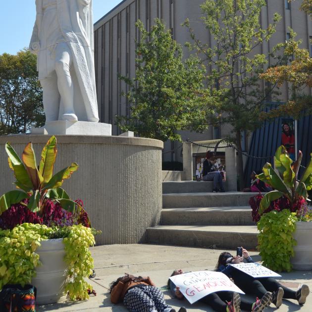 Student lying on ground beneath Columbus statue