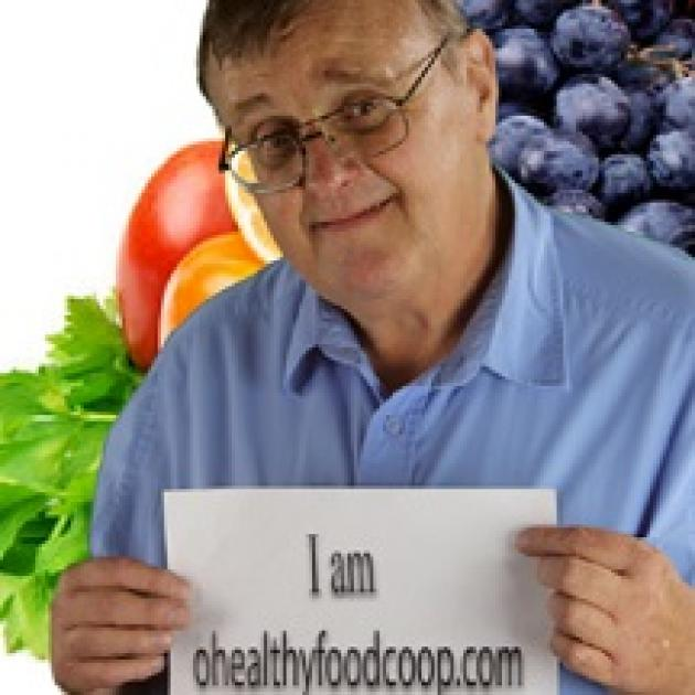 Older white man with glasses in front of fruits and vegetables holding a sign that reads I am healthyfoods.com