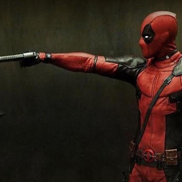 Deadpool character pointing a gun at a teddy bear