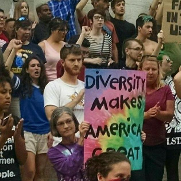 Person holding sign in crowd of people with fists in air, reading Diversity Makes America Great against tie-dyed background