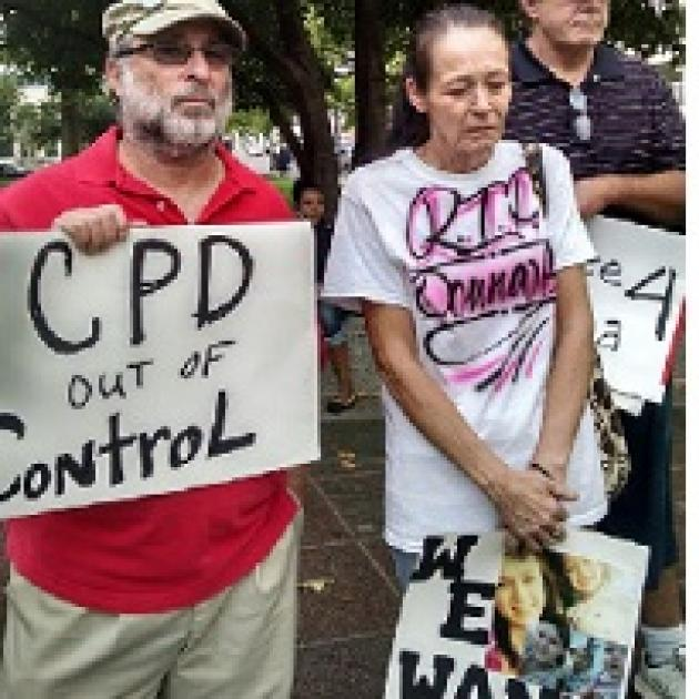 "Man with gray beard and sunglasses wearing a baseball cap holding a sign that says CPD out of control standing next to an older woman with gray hair pulled back in a ponytail looking down at the ground, very sad, wearing a white T-shirt with words ""RIP Donna"" on it and holding a sign with pictures of a young woman on it"