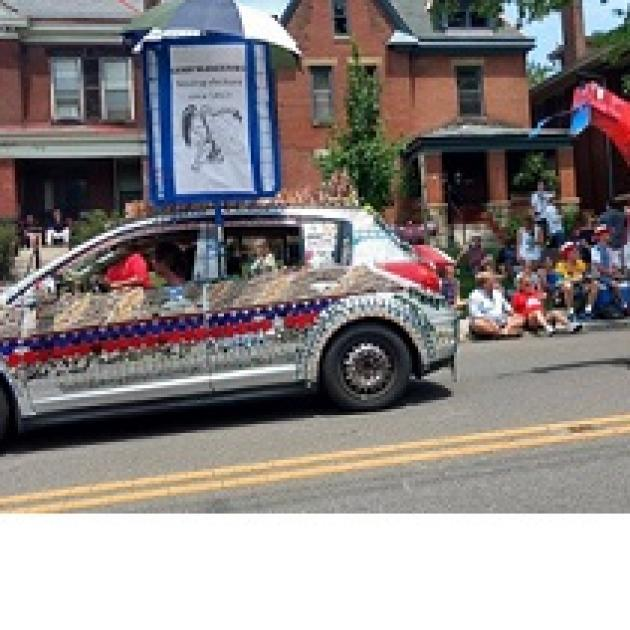 Decorated car and people sitting in front of houses watching