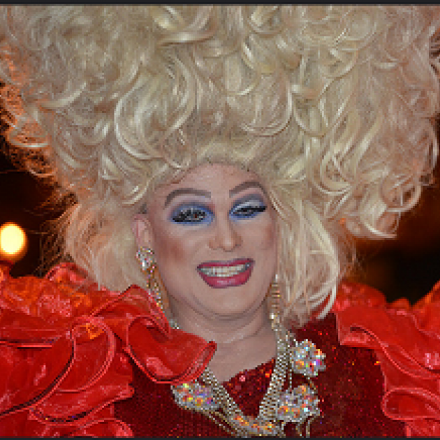 Man dressed a woman with huge blonde hair in curls going up in the air lots of blue eye shadow, red lips and a red outfit