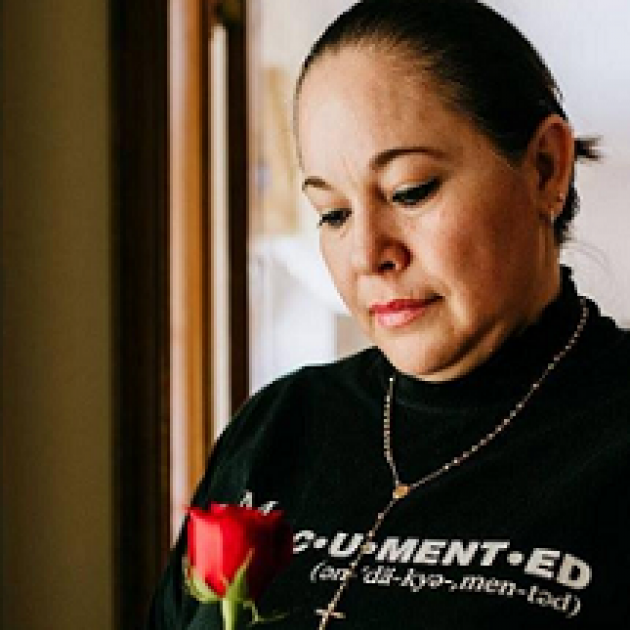 Latina woman looking down at a red rose in our hand