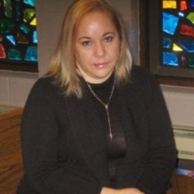 Young Latina woman with blonde hair and black clothes sitting on a pew in a church with stained glass windows behind her