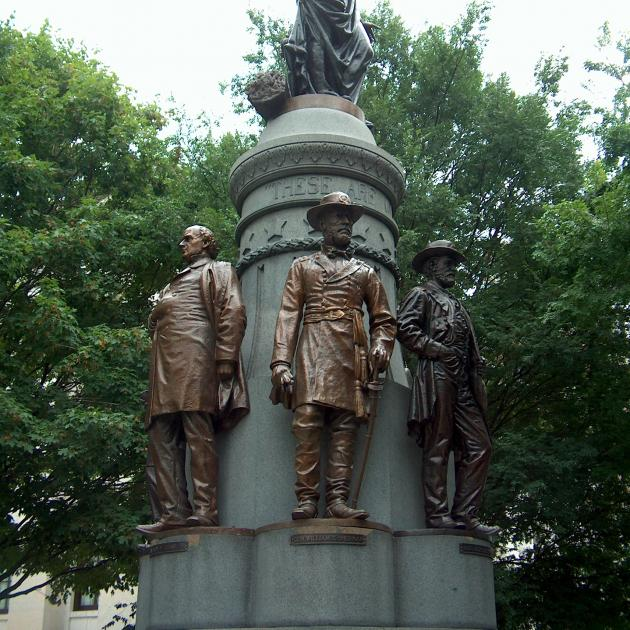 Gray pointy statue with Union Soldier figures standing with their backs around it against trees in the background
