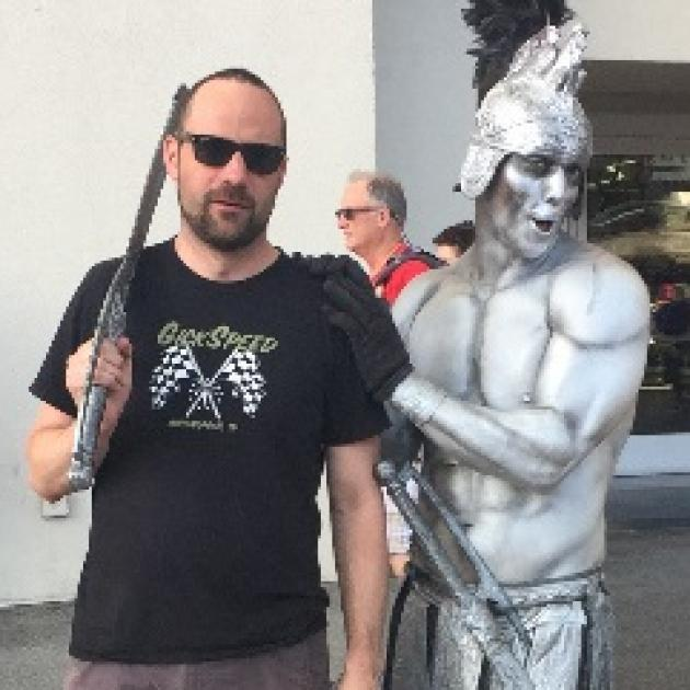 Guy with dark beard, sunglasses and sword next to a silver statue of a half-naked warrior with metal helmet