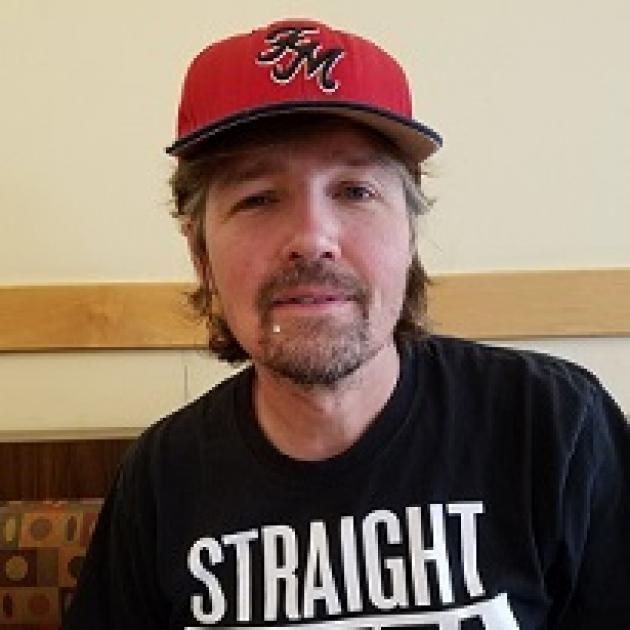 Man with brown hair sticking out from a red baseball cap and goatee wearing a black T-shirt