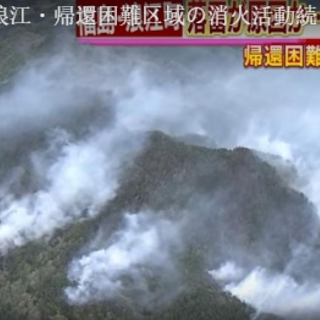 Looking down from sky at lots of smoke on ground with mountains and Japanese writing