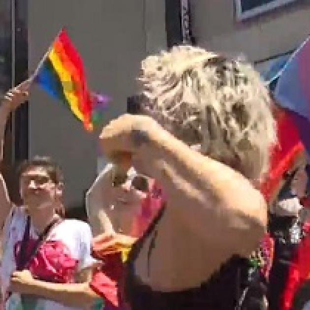 People dancing and a rainbow flag flying