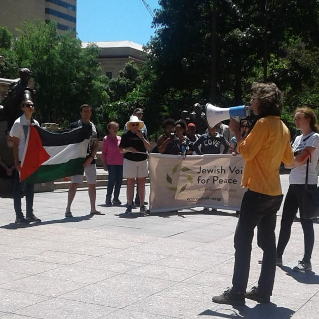 Man speaking into bullhorn and crowd with Jewish Voices for Peace sign