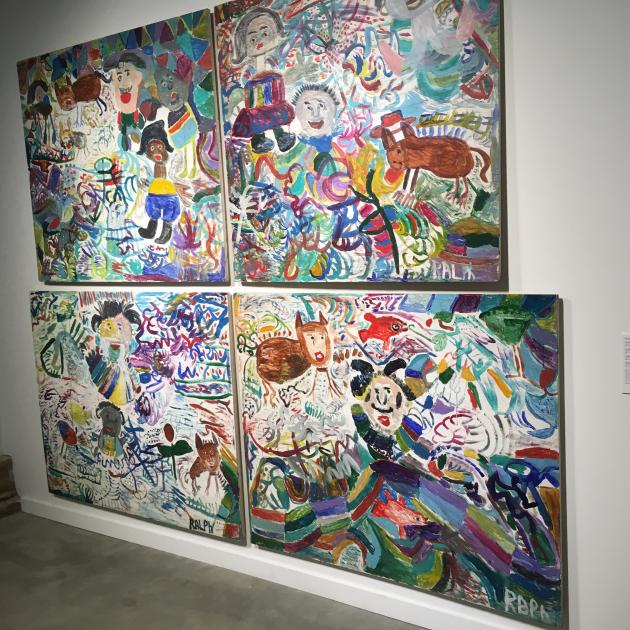Paintings hanging on a white wall that are very large one on top of the other and of very colorful scenes