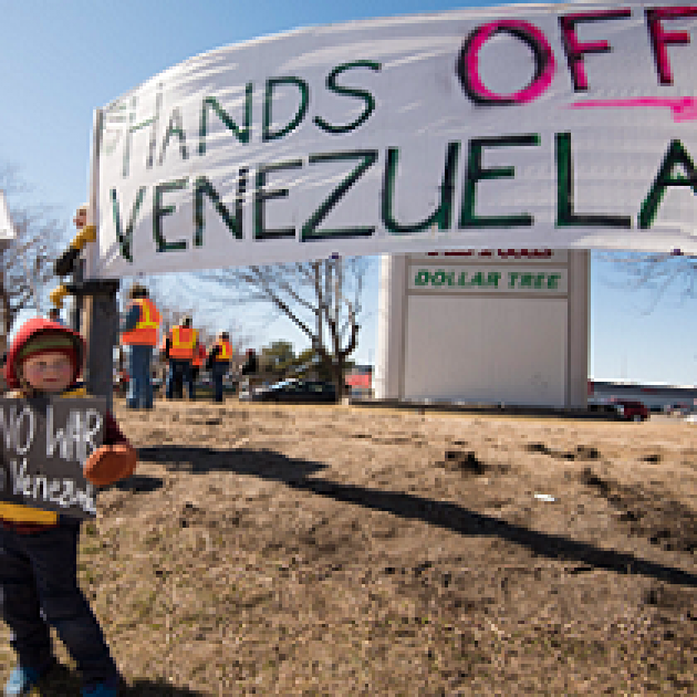 Big banner outside saying Hands off Venezuela and very small boy holding sign saying No War Venezuela