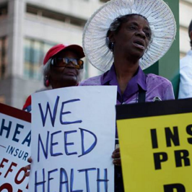 Woman holding sign saying We need Health Care